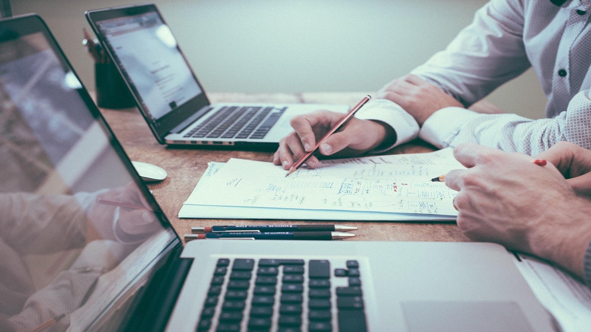 Na stole stoją otwarte dwa laptopy a recę dwóch osób znajdują się nad obszernymi notatkami.