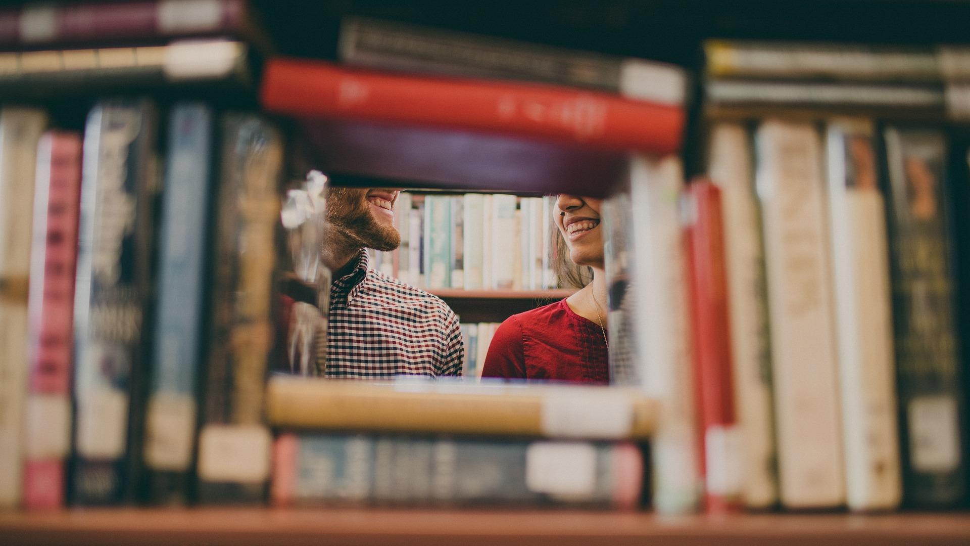Na pierwszym planie książki na półce. W wolnej przestrzeni między książkami widoczny fragment uśmiechniętej kobiety i mężczyzny.