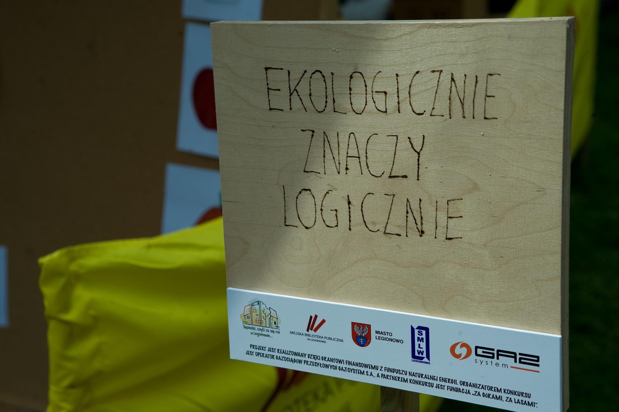 """Zdjęcie przedstawia tabliczkę z napisaem """"ekologicznie znaczy logicznie"""""""