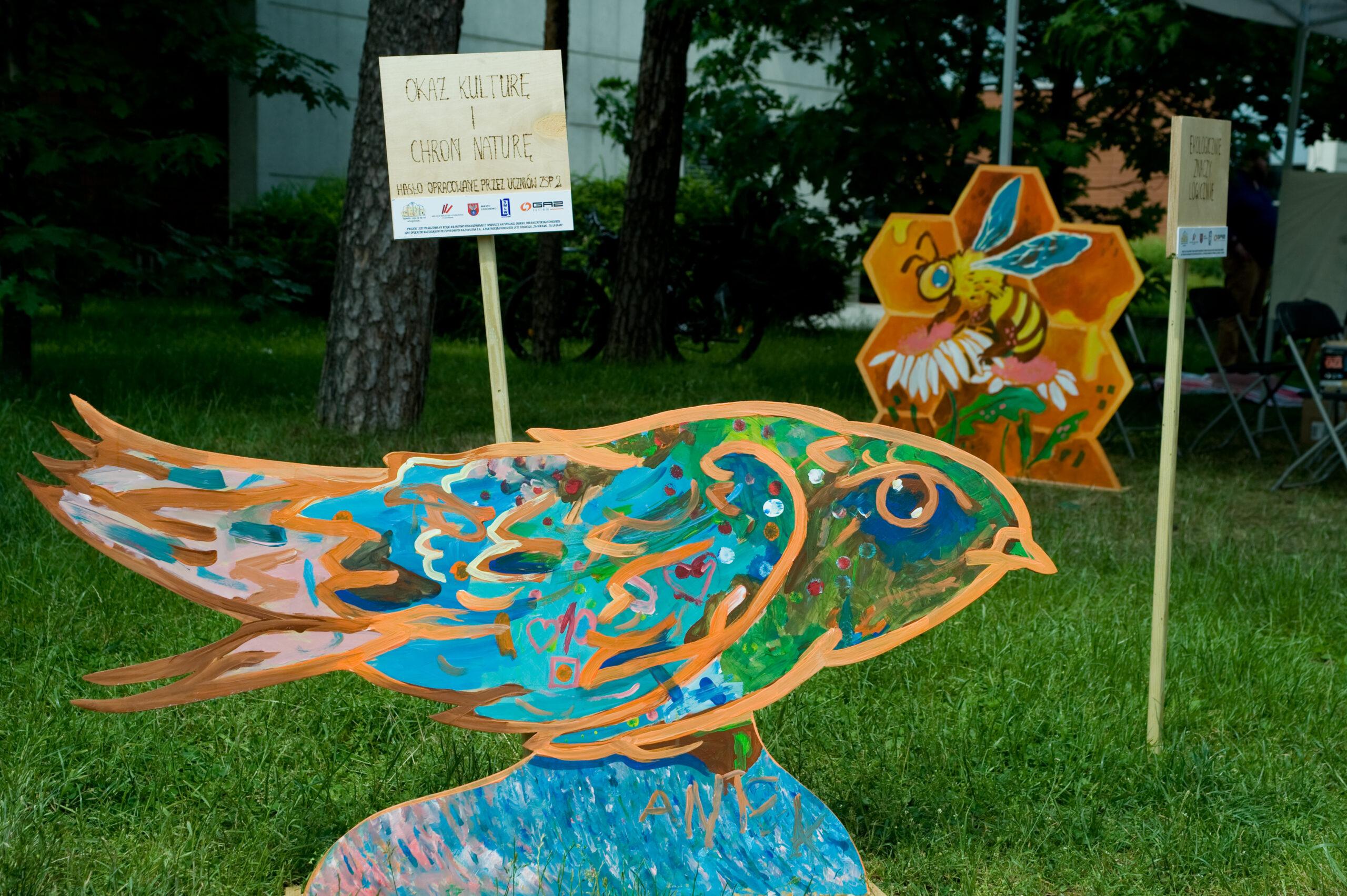 Zdjęcie przedstawia drewnianą, pomalowaną figurę ptaka, w tle tabliczka z hasłem ekologicznym i figura w kształce plastra miodu z namalowaną pszczołą w środku