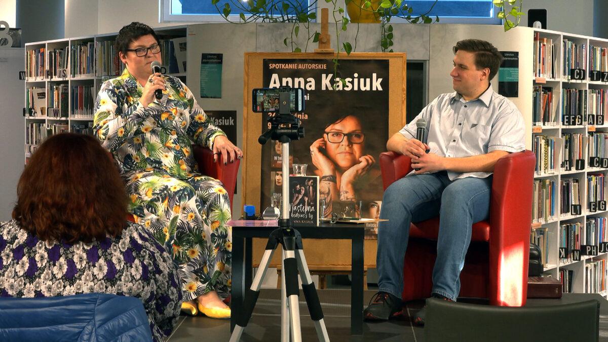 Zdjęcie przedstawia rozmawiającą autorkę, Annę Kasiuk z prowadzącym spotkanie bibliotekarzem na małej scenie wewnątrz biblioteki