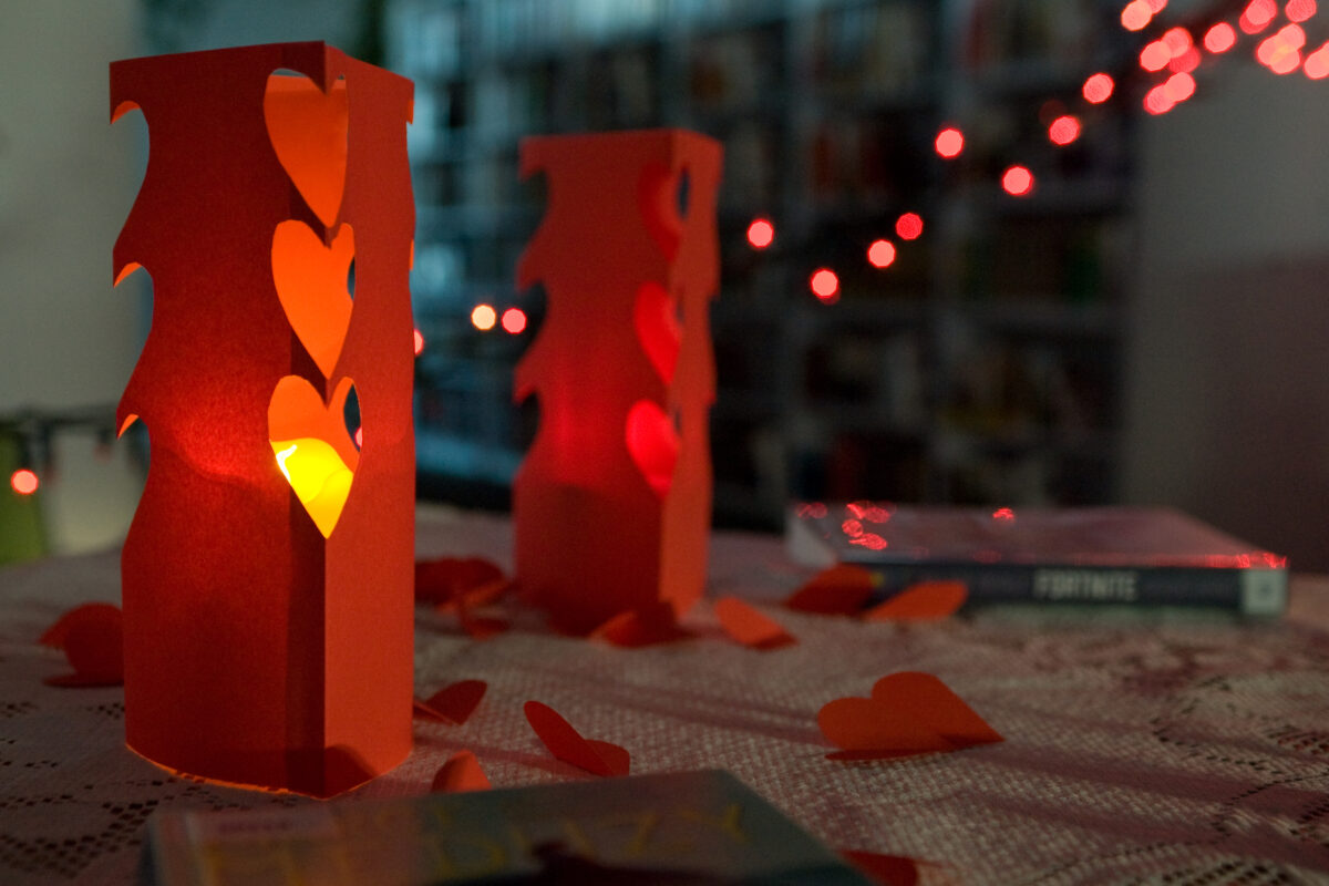 Wycięte czerwone lampiony z bloku rysunkowego, wzdłuż kominku wycięte serduszka a w środku świecąca się świeczka.